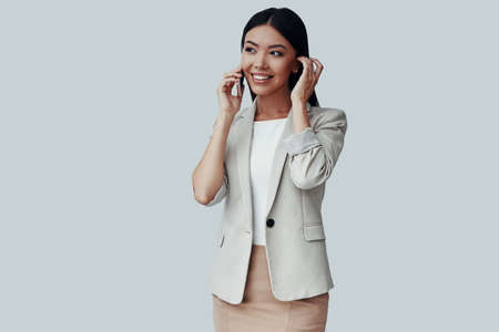 Always available. Attractive young Asian woman talking on the phone and smiling while standing against grey background