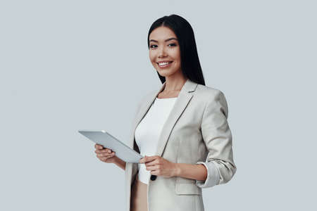 Young and smart. Attractive young Asian woman using digital tablet and smiling while standing against grey background Imagens