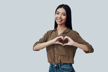 Heart shape. Beautiful young Asian woman looking at camera and smiling while standing against grey background