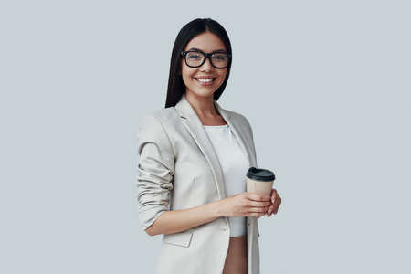 Coffee break. Attractive young Asian woman looking at camera and smiling while standing against grey background Imagens