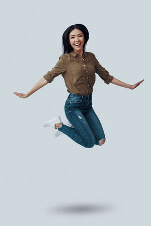 Totally free. Full length of beautiful young Asian woman looking at camera and smiling while hovering against grey background