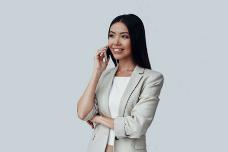 Good business talk. Attractive young Asian woman talking on the phone and smiling while standing against grey background Imagens