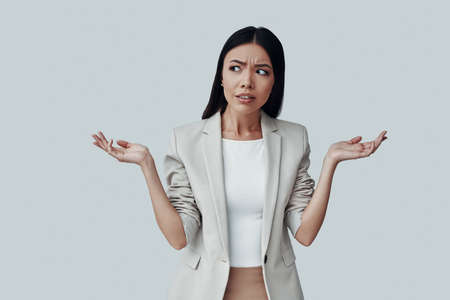 What to do? Confused young Asian woman gesturing and making a face while standing against grey background