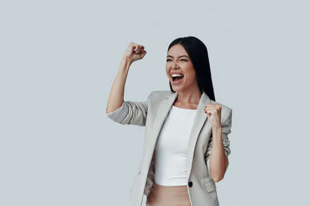 I won! Attractive young Asian woman gesturing and smiling while standing against grey background