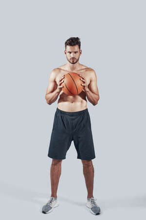 Full length of handsome young man in sports clothing carrying basketball ball and looking at camera while standing against grey background 写真素材