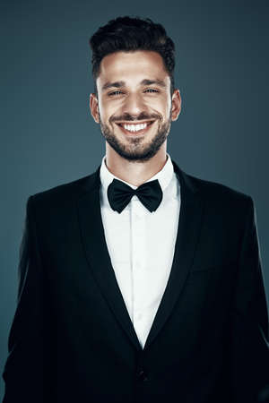 Charming young man in bow tie looking at camera and smiling while standing against grey background Zdjęcie Seryjne