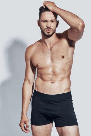 Bel giovane uomo a torso nudo che guarda l'obbiettivo mentre in piedi su sfondo grigio