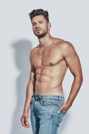 Handsome young shirtless man looking at camera while standing against grey background