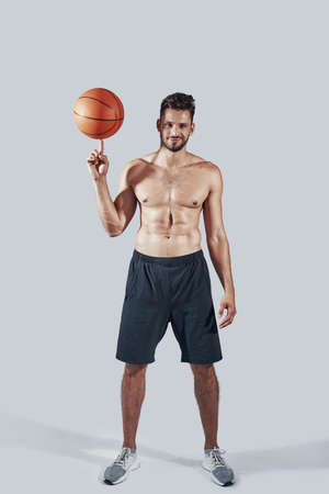 Full length of handsome young man in sports clothing spinning on finger basketball ball and smiling while standing against grey background Zdjęcie Seryjne