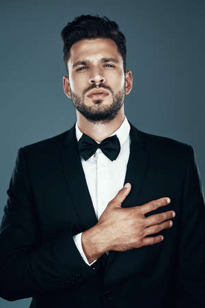Charming young man in bow tie looking at camera and keeping hand on heart while standing against grey background