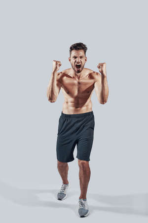 Full length of handsome young man in sports clothing gesturing and shouting while standing against grey background