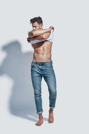 Per tutta la lunghezza del bel giovane che si toglie la maglietta mentre si trova su uno sfondo grigio