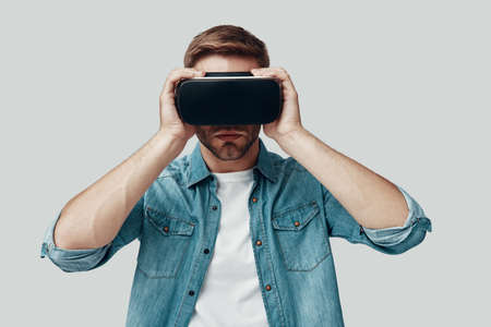 Handsome young man using virtual reality simulator while standing against grey background