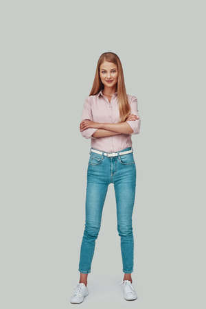 ll length of attractive young woman looking at camera and smiling while standing against grey background Stock fotó