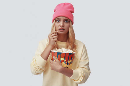 Attractive young woman eating popcorn and looking at camera while standing against grey background Banco de Imagens