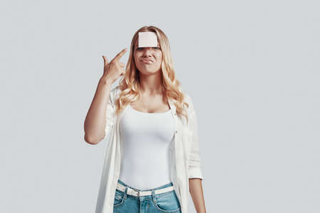 Confused young woman aiming with handgun and making a face while standing against grey background Banco de Imagens