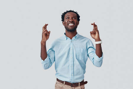Handsome young African man crossing fingers and smiling while standing against grey background Imagens