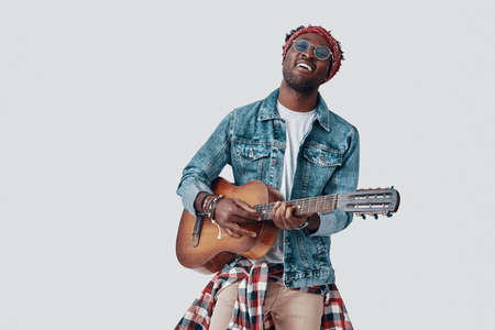 Handsome young African man playing guitar and smiling while standing against grey background Imagens