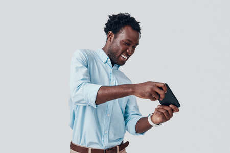 Handsome young African man playing mobile game and smiling while standing against grey background Imagens