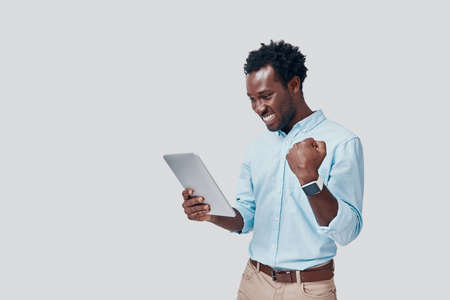 Handsome young African man using digital tablet and cheering while standing against grey background