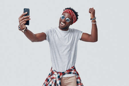 Handsome young African man taking selfie and smiling while standing against grey background Imagens