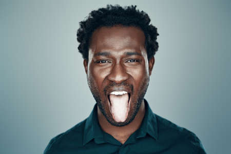 Handsome young African man looking at camera and sticking out tongue while standing against grey background