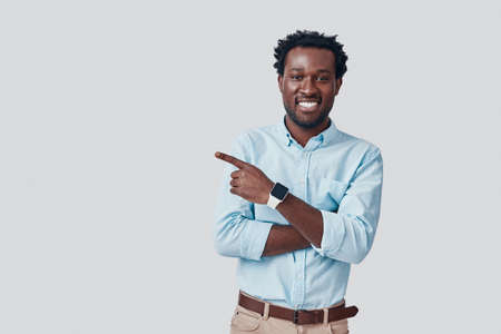 Handsome young African man pointing copy space and smiling while standing against grey background