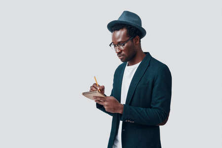 Handsome young African man writing something down while standing against grey background