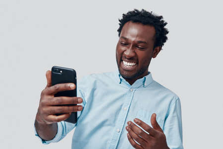 Handsome young African man talking using video conference and smiling while standing against grey background