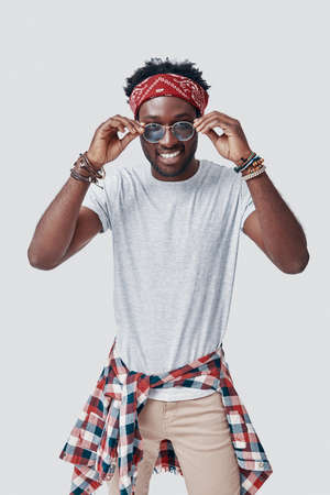 Handsome young African man adjusting his eyewear and looking at camera while standing against grey background Imagens