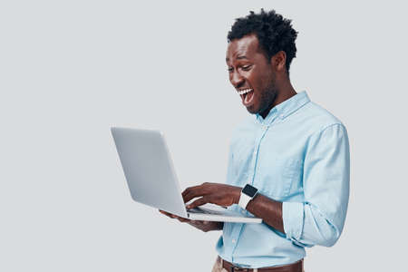 Handsome young African man using laptop and smiling while standing against grey background