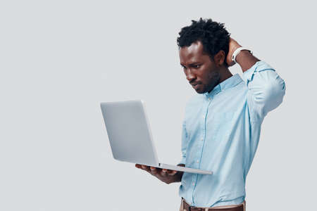 Handsome young African man using laptop while standing against grey background