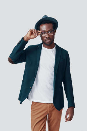 Handsome young African man adjusting eyewear and looking at camera while standing against grey background Imagens