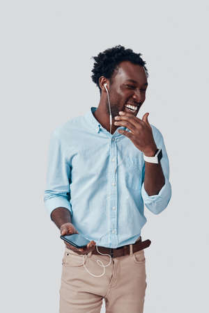 Handsome young African man listening music and smiling while standing against grey background