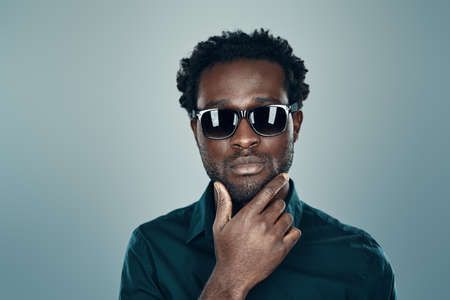 Handsome young African man in eyewear looking at camera and keeping hand on chin while standing against grey background