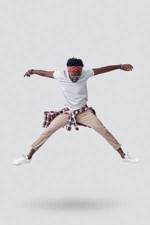 Full length of playful young African man going crazy while hovering against grey background Imagens