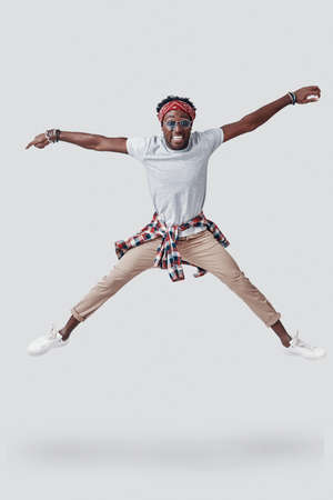Full length of playful young African man smiling and looking at camera while hovering against grey background