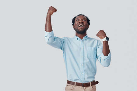Handsome young African man gesturing and smiling while standing against grey background