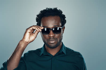 Handsome young African man looking at camera and adjusting eyewear while standing against grey background Imagens