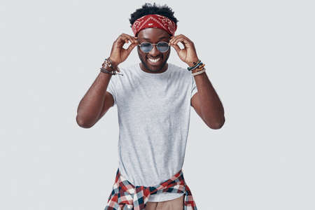 Handsome young African man adjusting his eyewear and smiling while standing against grey background Imagens