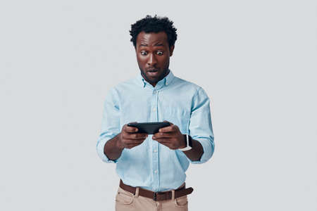 Handsome young African man playing mobile game while standing against grey background Imagens