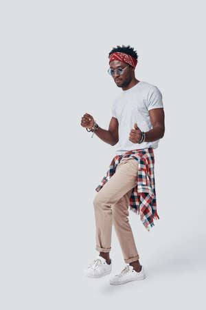Full length of playful young African man dancing while standing against grey background