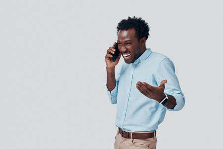 Handsome young African man talking on the phone and smiling while standing against grey background