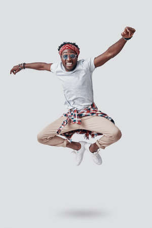Full length of playful young African looking at camera and smiling while hovering against grey background Imagens
