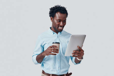 Handsome young African man using digital tablet and smiling while standing against grey background