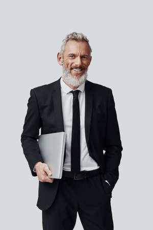 Confident mature man in full suit carrying laptop and smiling while standing against grey background Imagens