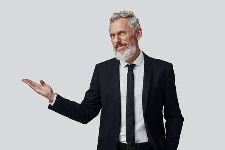 Confident mature man in full suit pointing copy space and looking at camera while standing against grey background