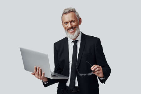 Confident mature man in full suit working using laptop and smiling while standing against grey background
