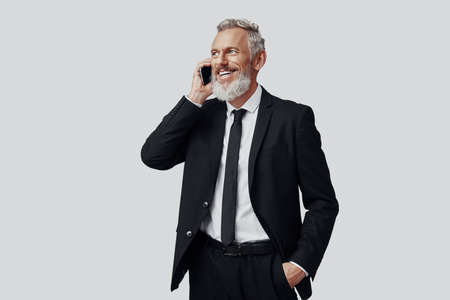 Happy mature man in full suit talking on the phone and smiling while standing against grey background Imagens