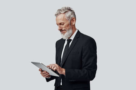 Thoughtful mature man in full suit working using digital tablet and smiling while standing against grey background